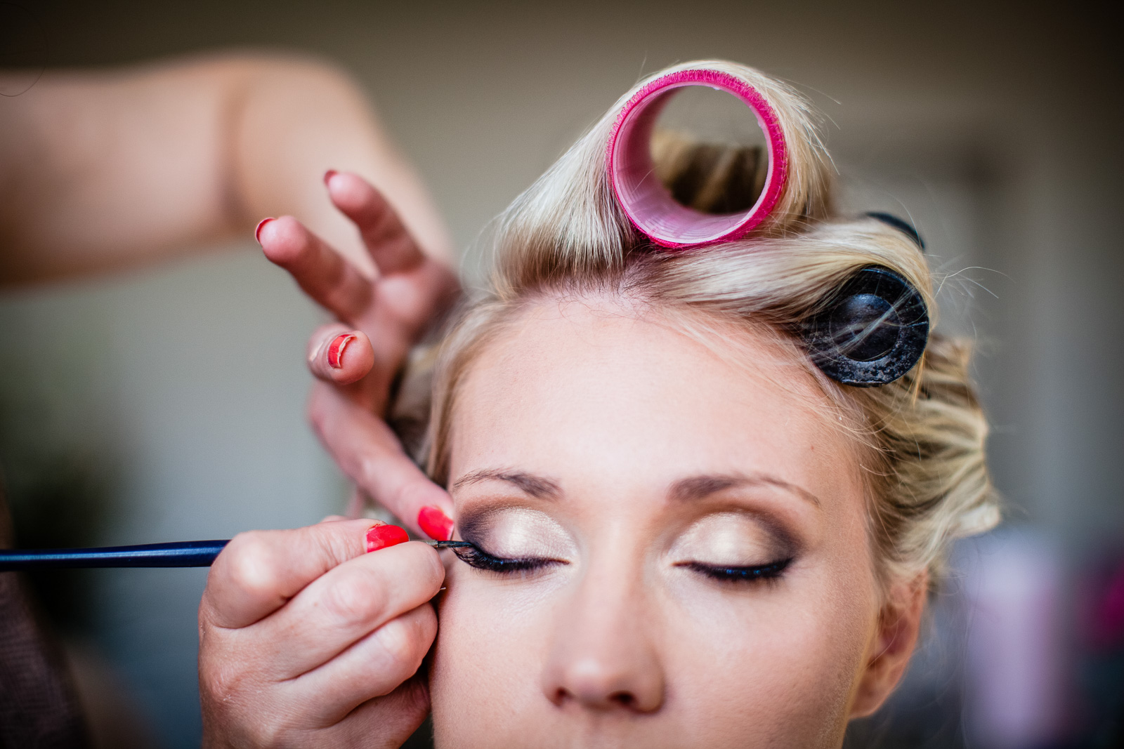 hair in rollers and makeup artist putting on brides eyelashes - shropshire wedding photographer