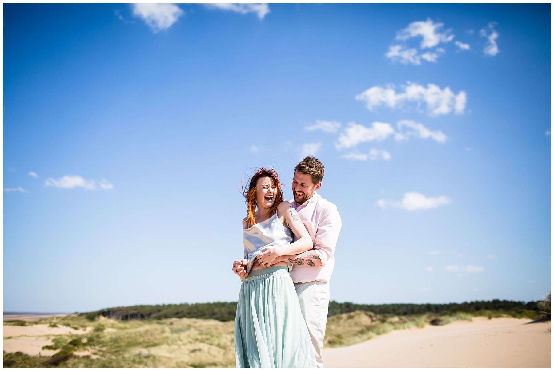 blue sky and couple laughing at beach engagement shoot - charlotte giddings photography