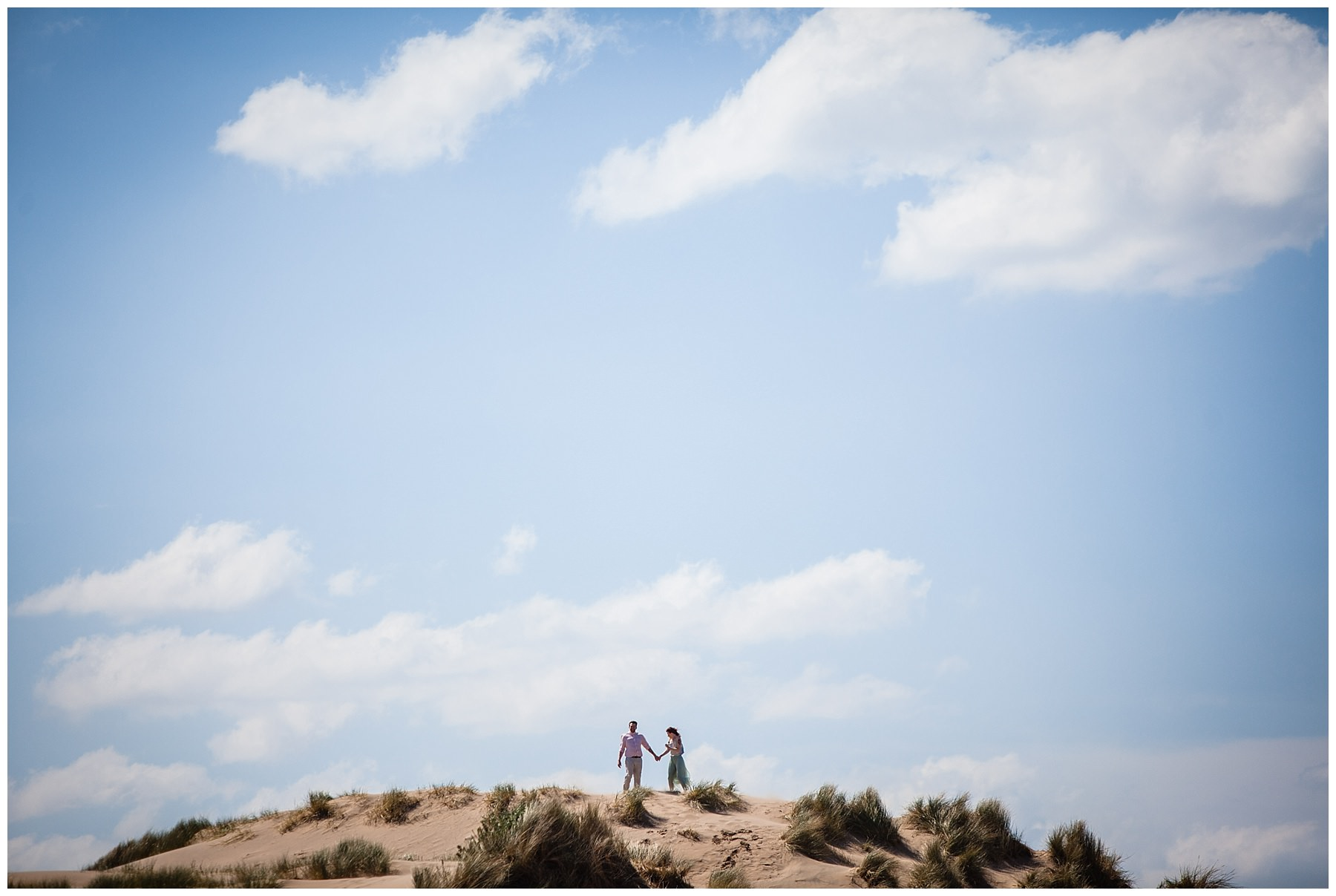 couple on top of a high dune at formby beach engagement shoot