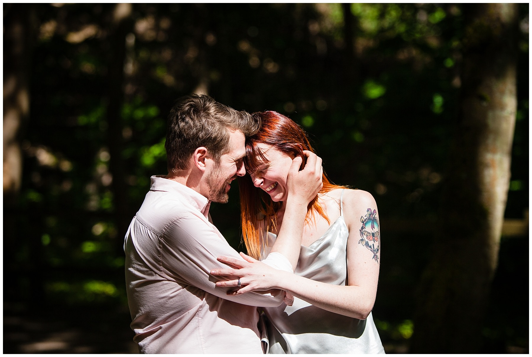 couple giggling in the woods at formby photo shoot - charlotte giddings photography
