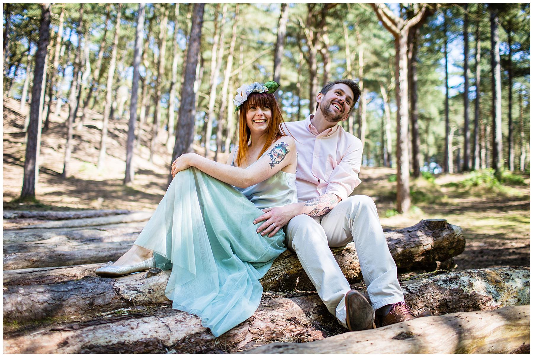 couple sat on logs in formby beach woodland area - wedding photographer shropshire