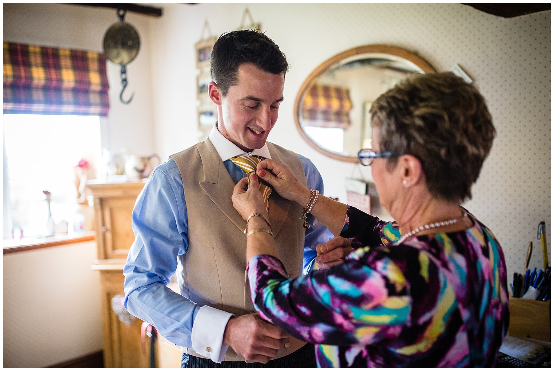mother of the groom helping groom with his tie - shropshire marquee wedding