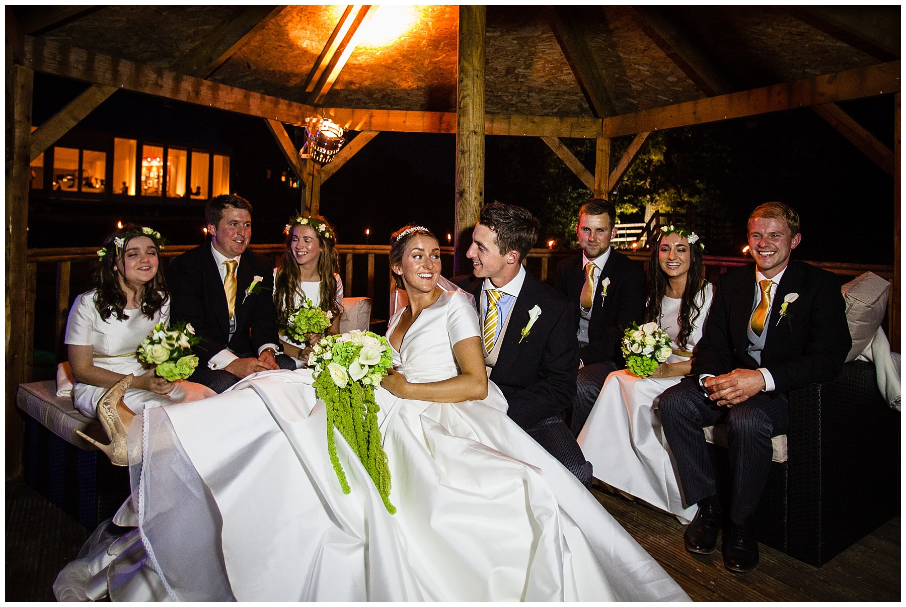 bride and groom giggling with the ushers and best man in summer house at shropshire marquee wedding