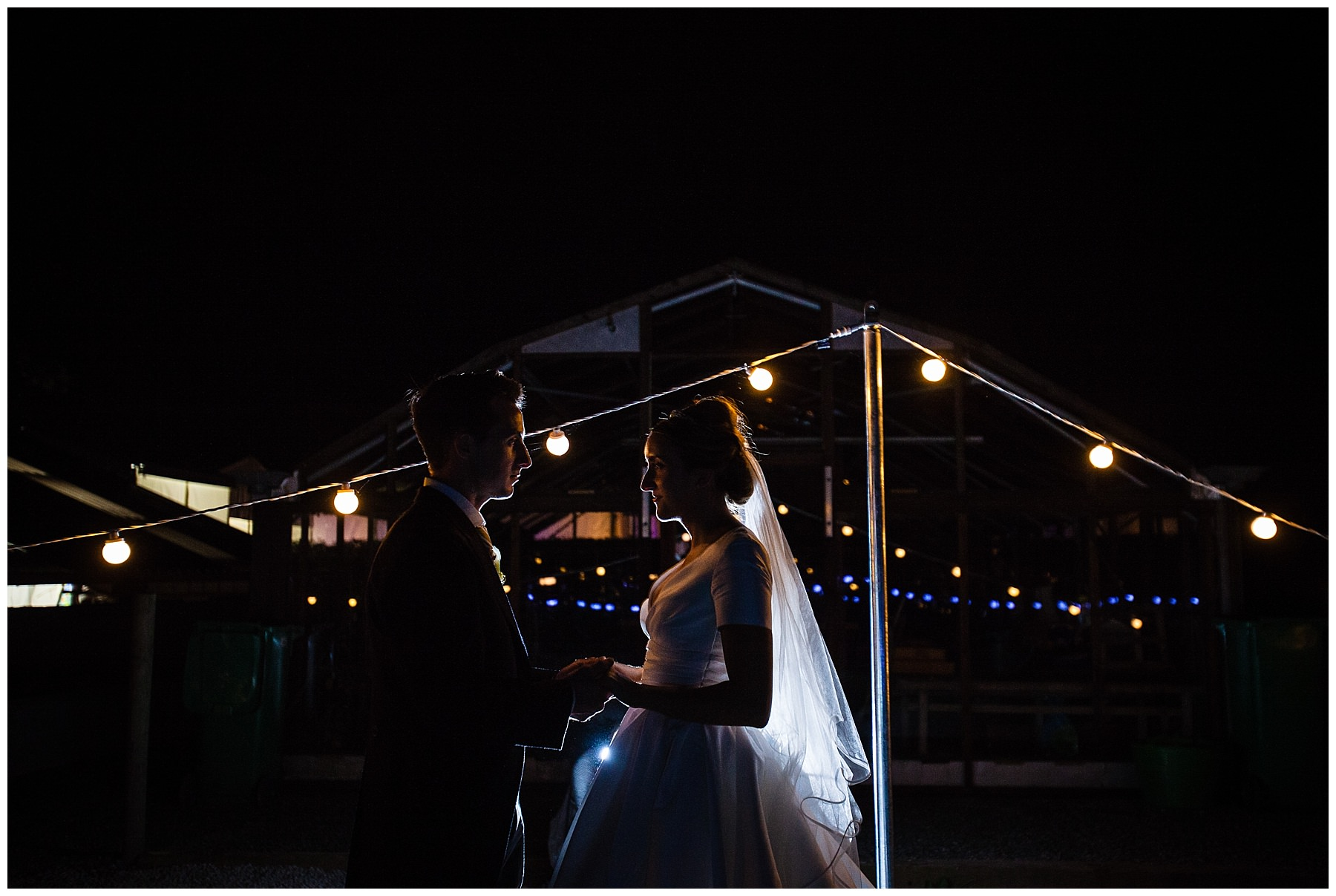 final shot of bride and groom in the evening with twinkly lighting