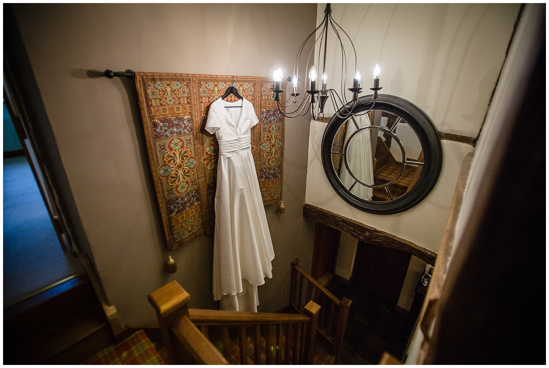 bespoke wedding dress hanging in hallway at shropshire home