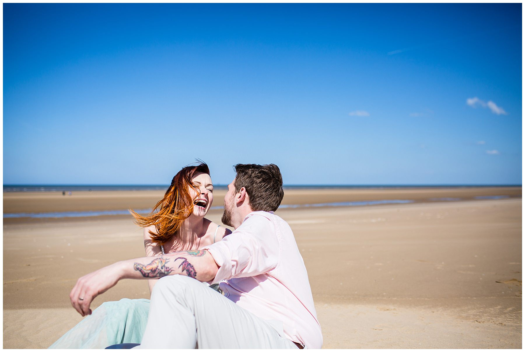couple sat on formby beach laughing - charlotte giddings photography