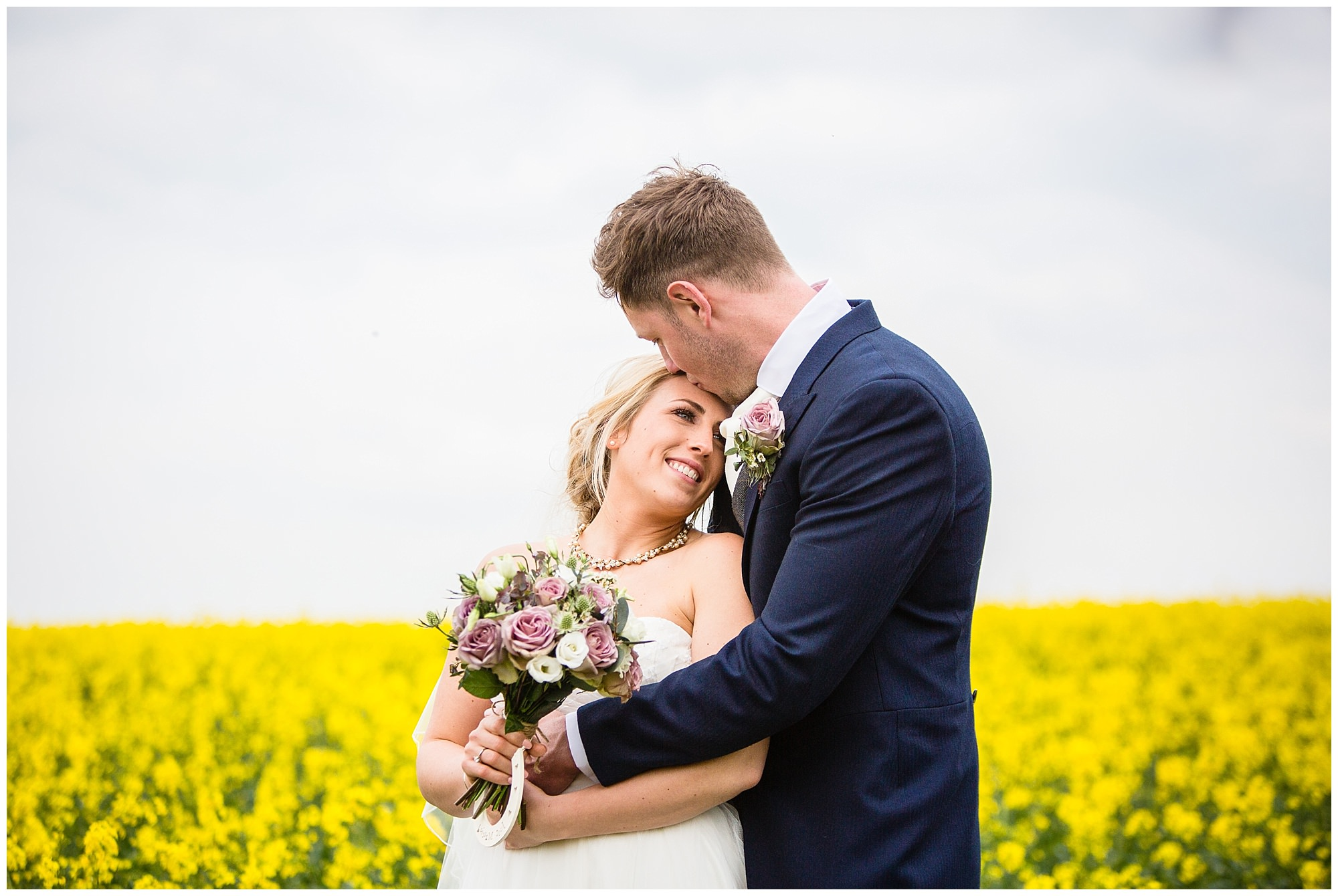 bride and groom close together in rape seed field