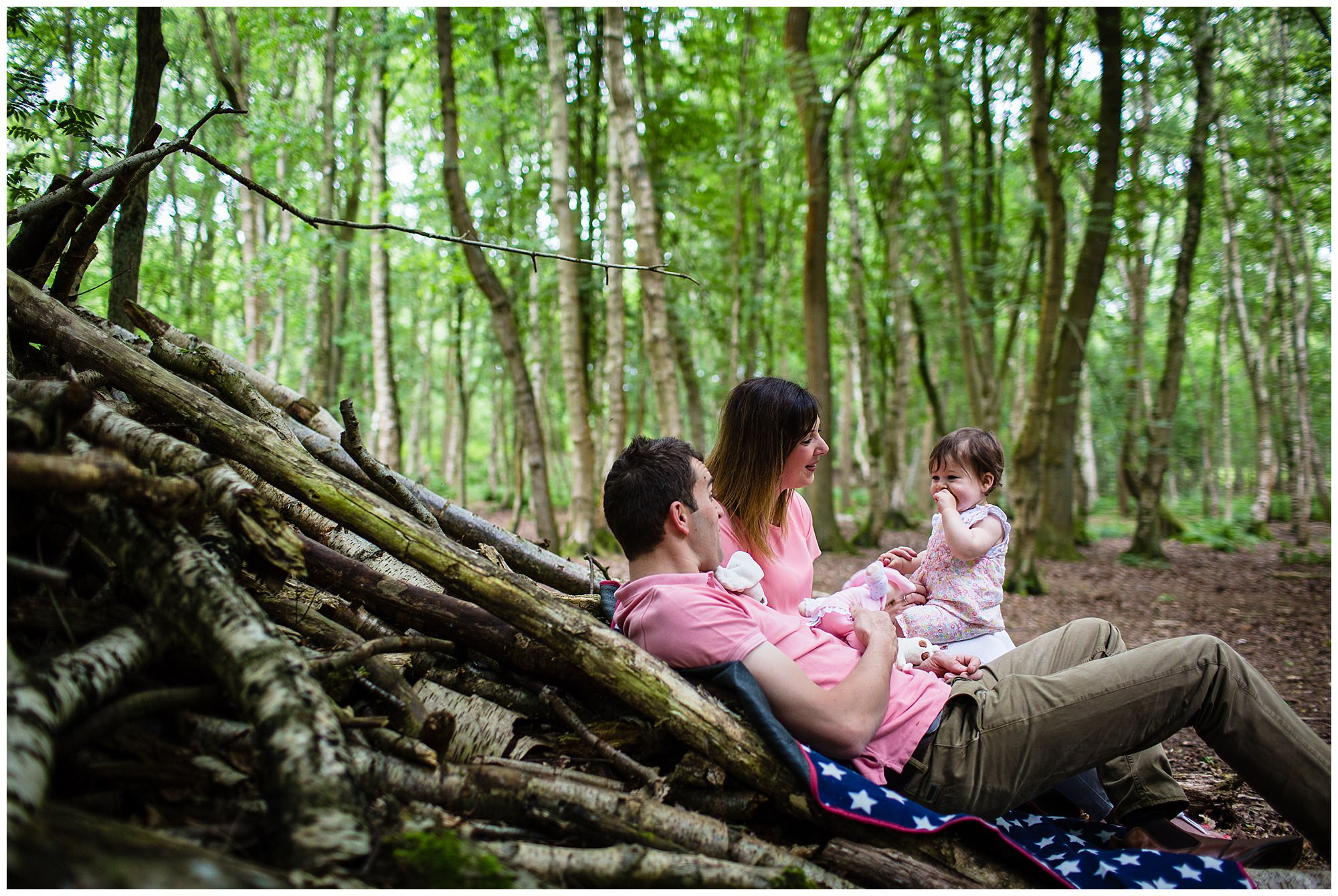 natural moment of mum and dad playing and talking with baby girl - brown moss, shropshire