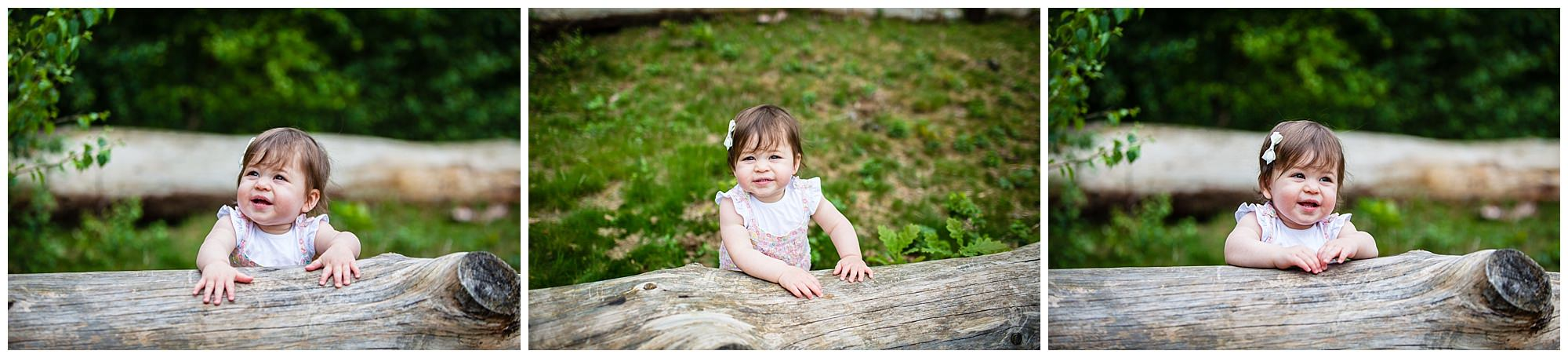 baby girl looking at the camera whioe supporting herself on a log