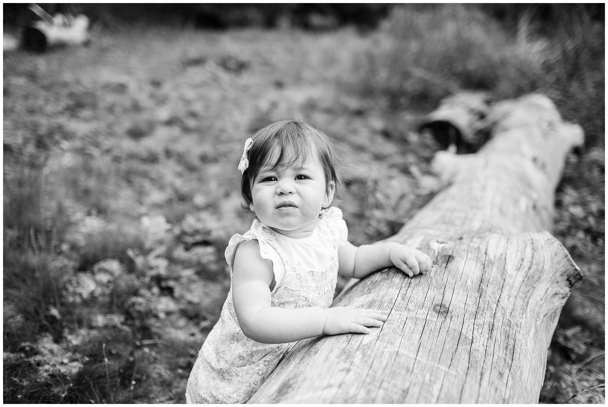 beautiful black and white photo of 1 year old girl supporting herself looking at the camera