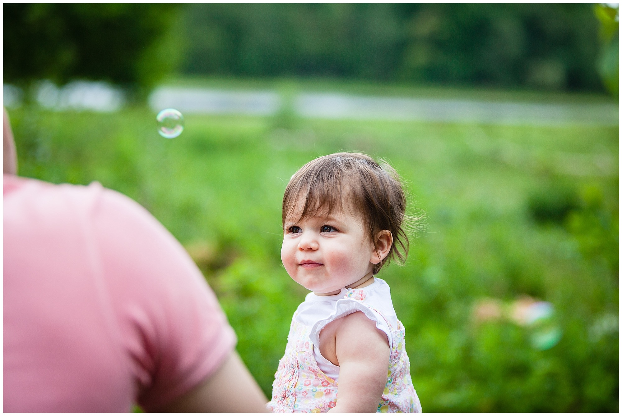 baby girl watching bubbles being blown by her mummy - family