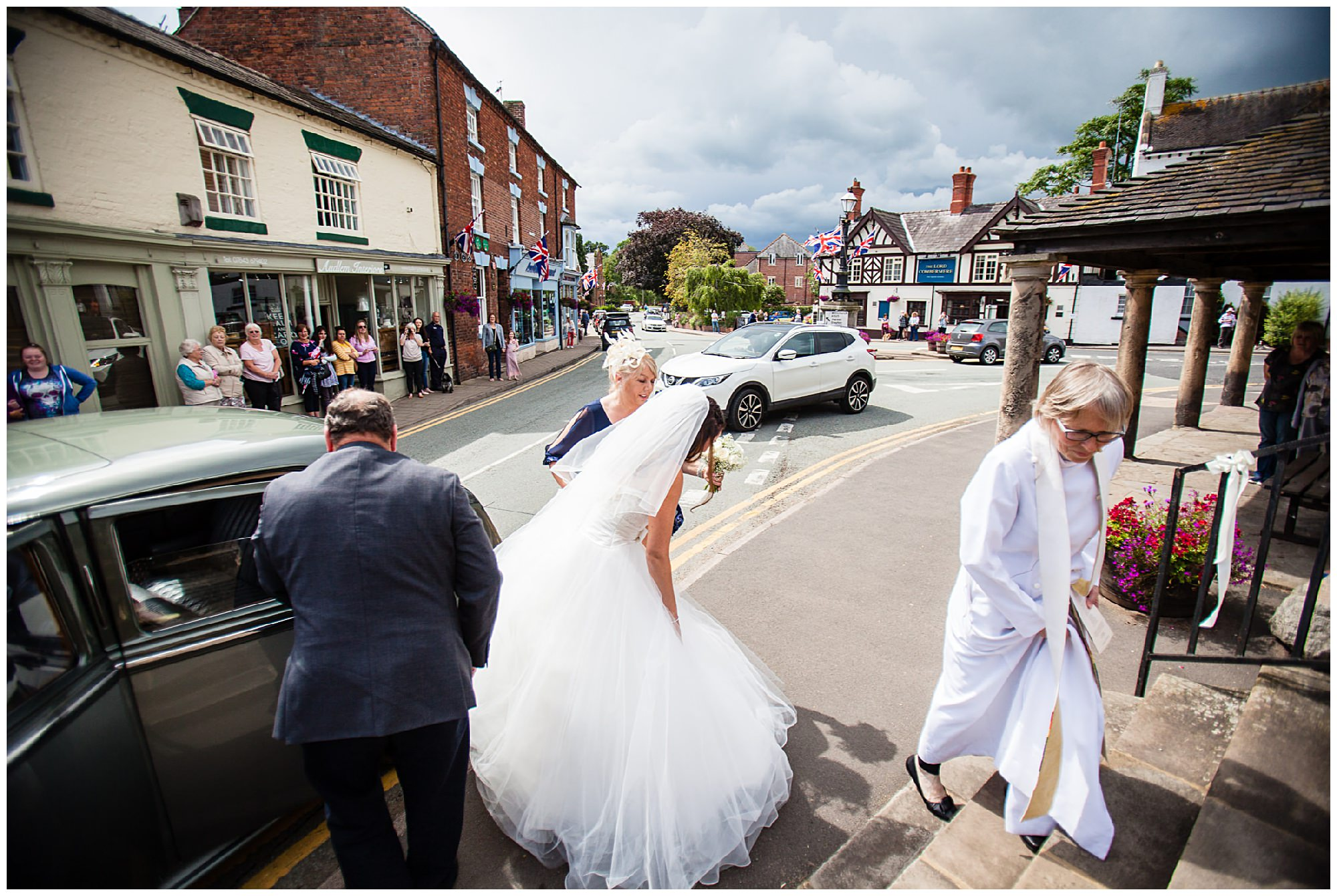 St James' Church Audlem Wedding Photography bride getting ready to go up the steps at stjames church audlem cheshire