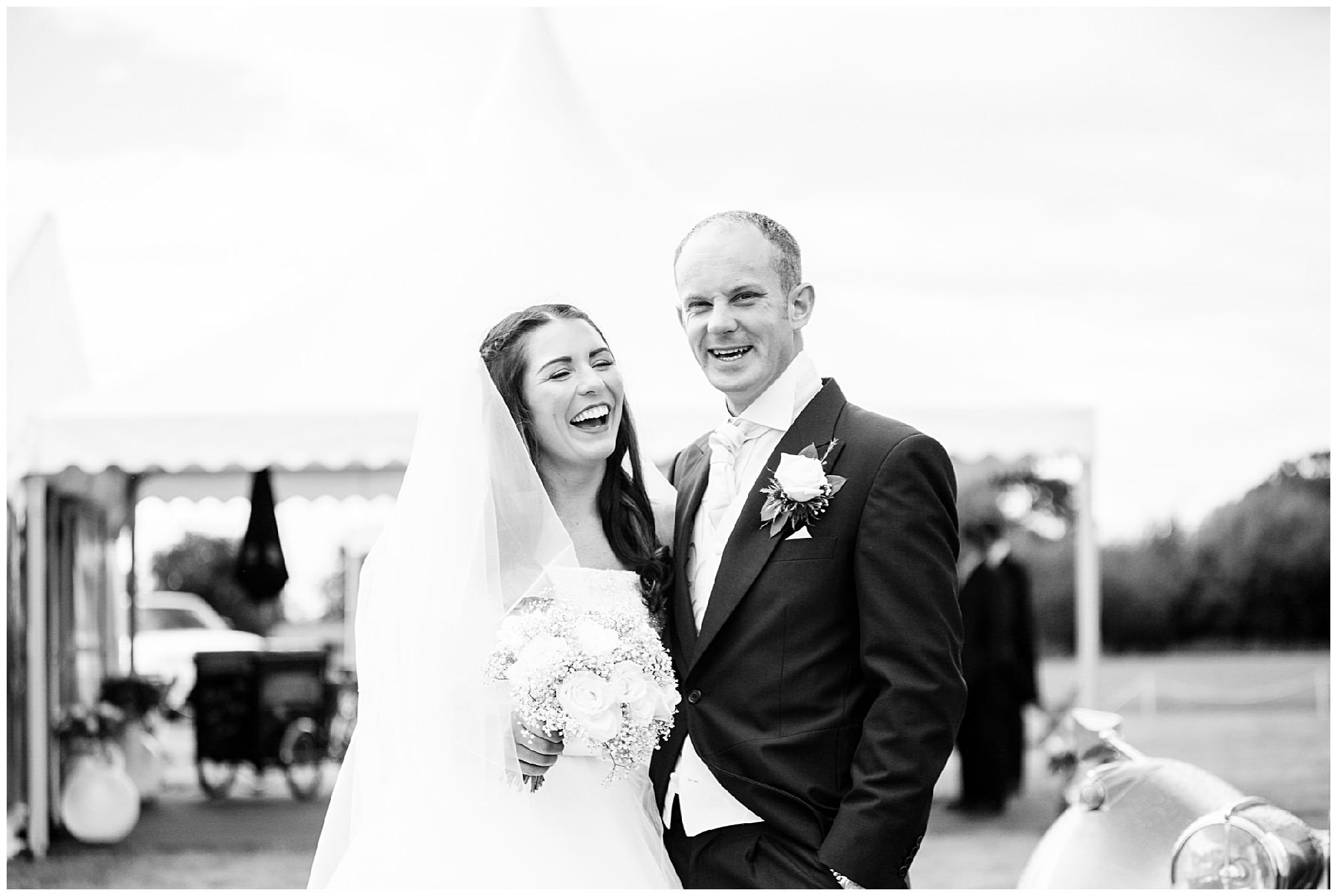 bride and groom laughing together at marquee wedding venue
