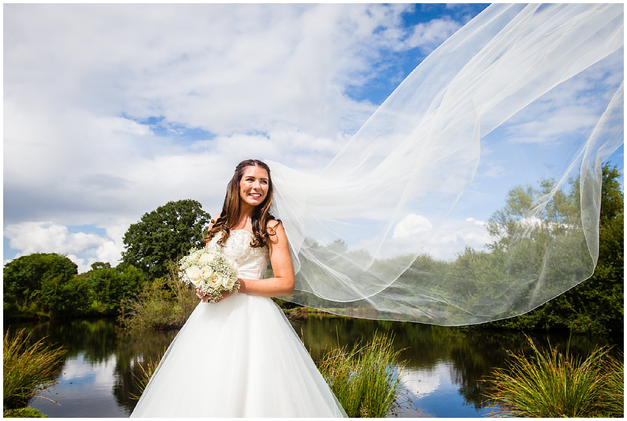 bride by a lake with veil in the air with blue sky backdrop