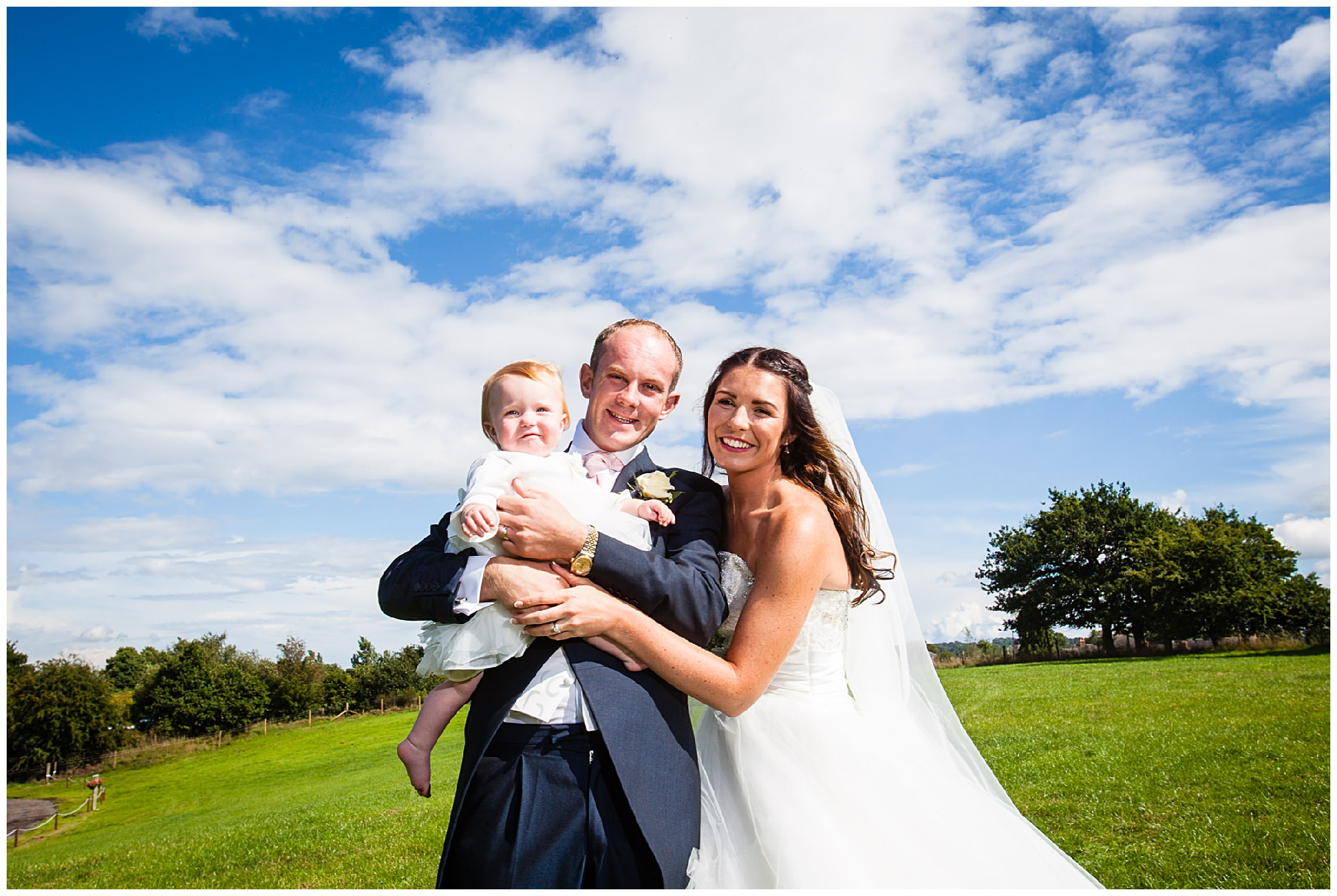 bride and groom with their daughter at their home marquee wedding - St James' Church Audlem Wedding Photography