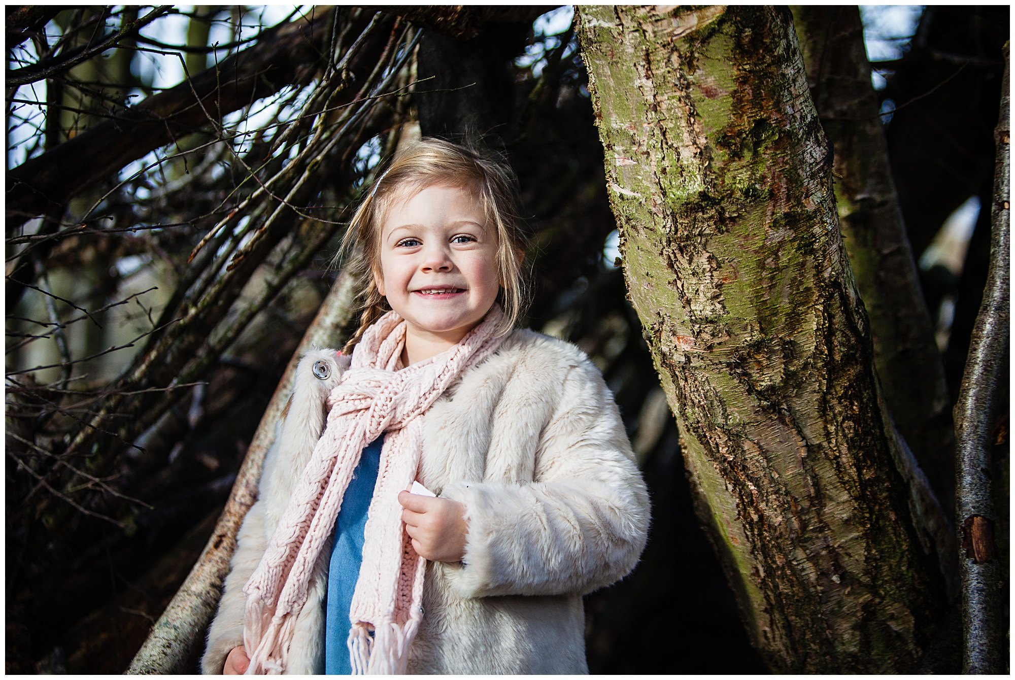 little girl looking happy smiling in a stick den