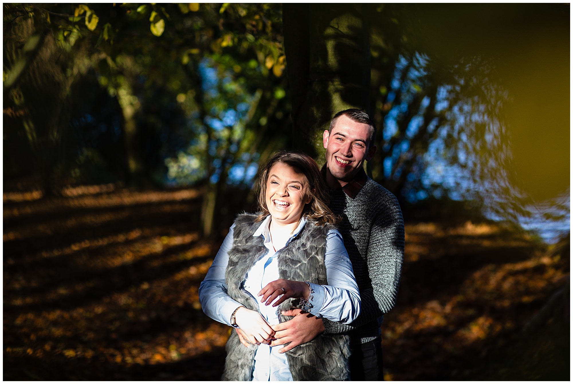 coupleat Colemere laughing amongst autumn leaves - Shropshire Engagement Photographer