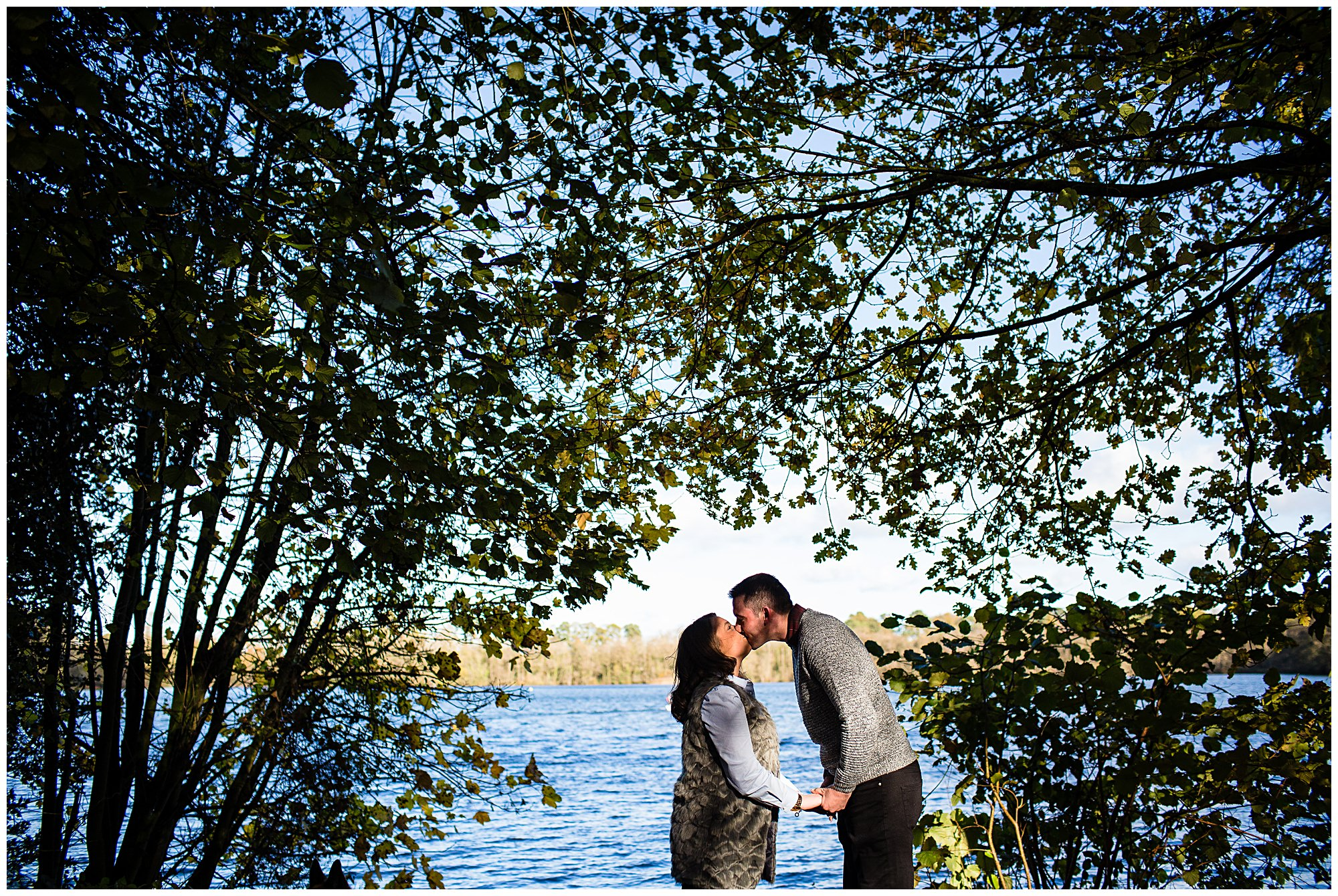 couple kissing with colemere mere in the background - shropshire photographer