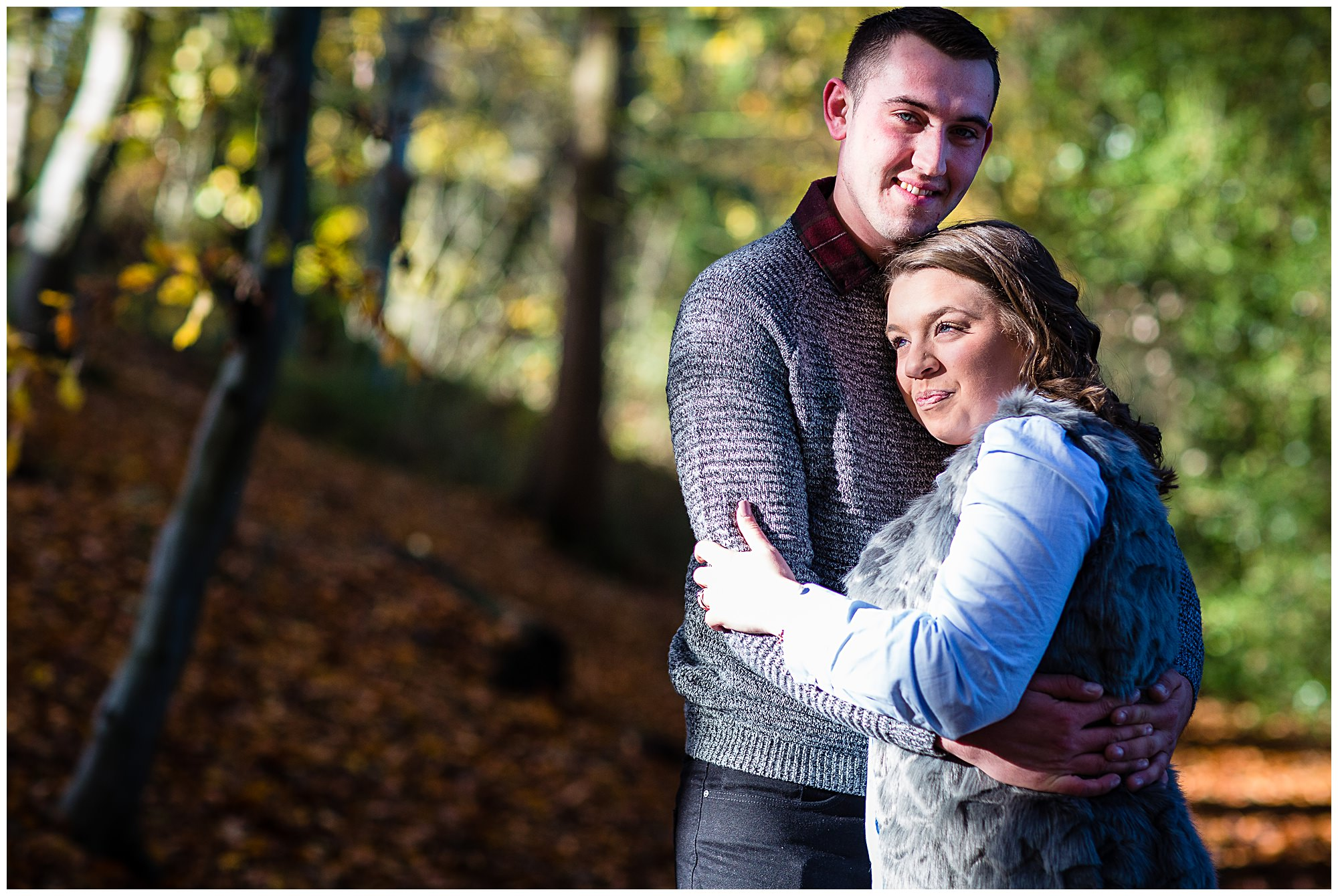 kirsty and luke cuddling while luke looks at the camera smitten - Shropshire Engagement Photographer