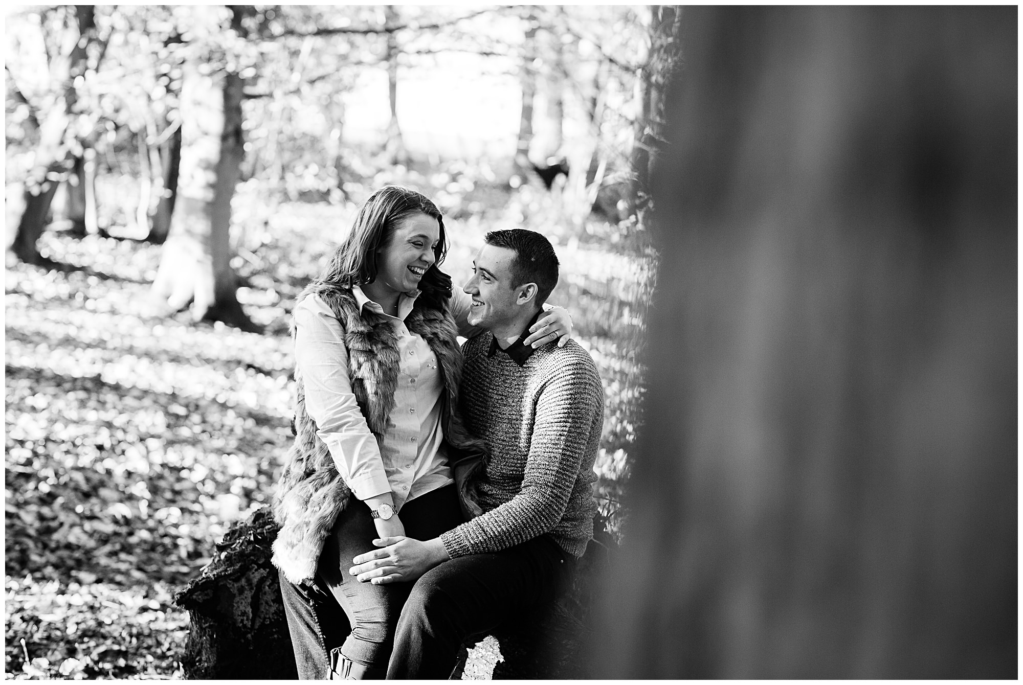 couple sat down on a log at colemere laughing at each other looking happy and in love