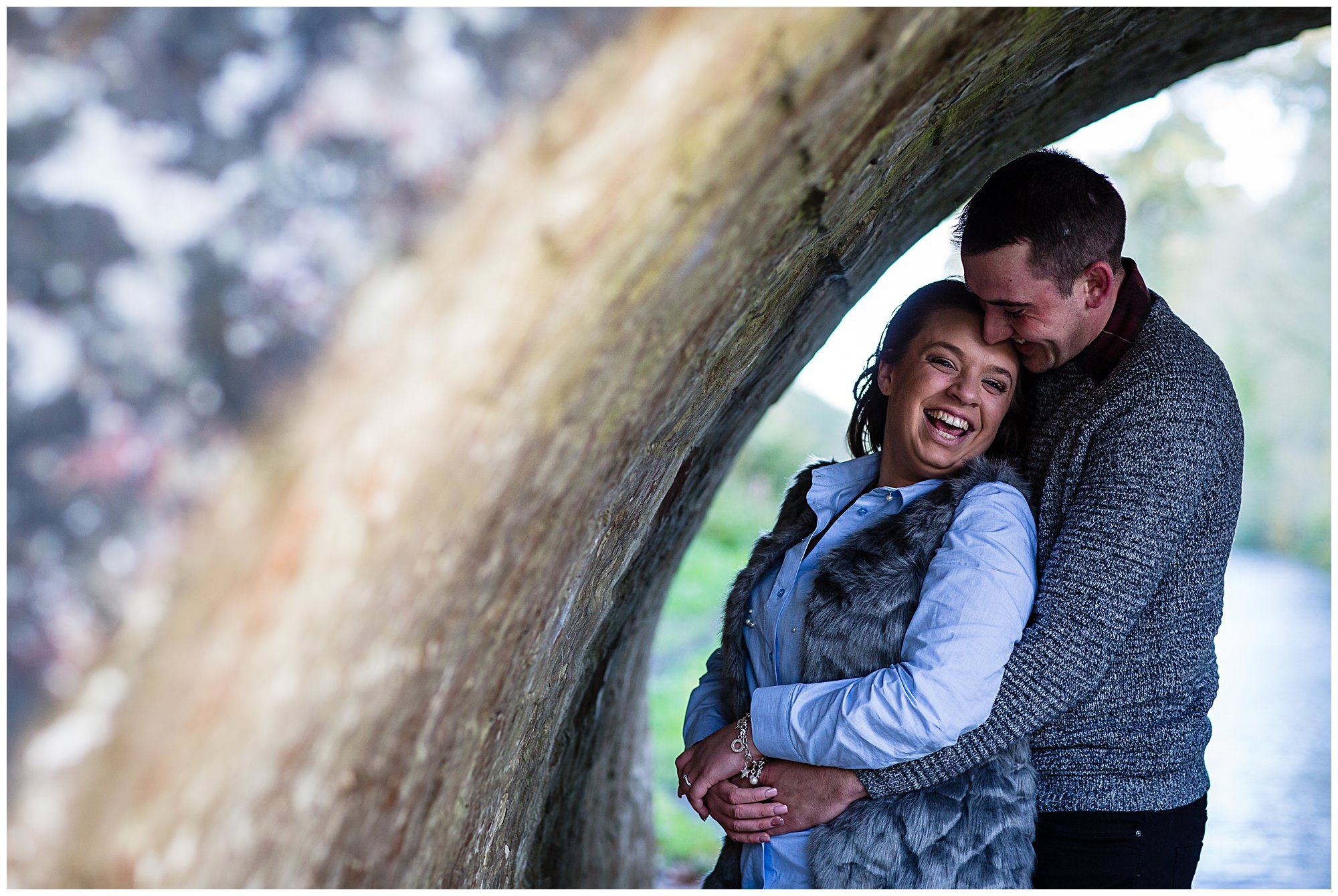 couple giggling as they take cover under the bridge at colemere - shropshire engagement photographer