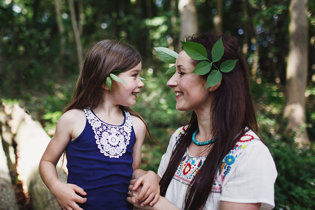 charlotte giddings photographer looking at daughter lovingly with leaves in their ears - photographing weddings and families in Shropshire,