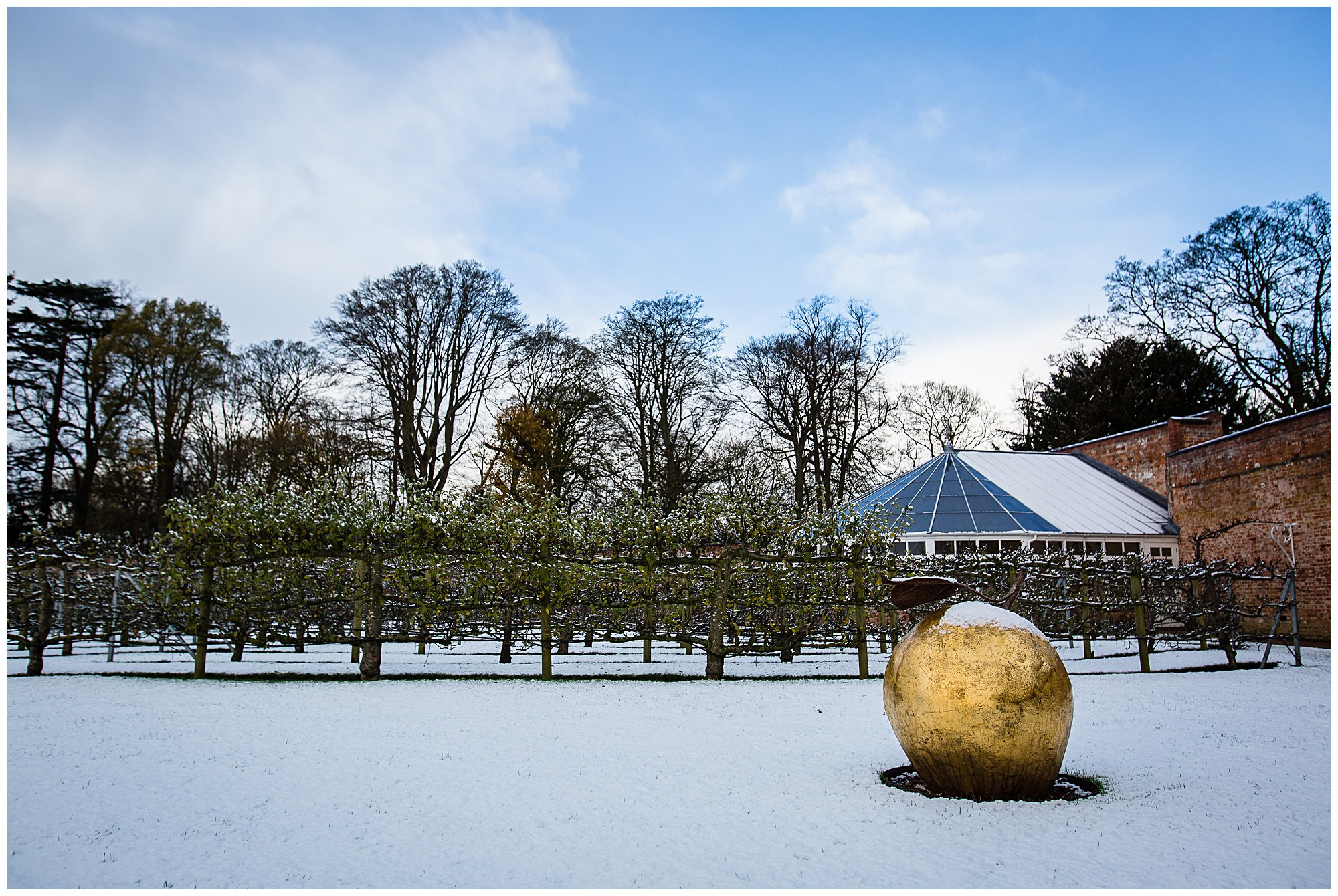 glasshouse in the snow with gold apple - Shropshire Wedding Venues in the Snow