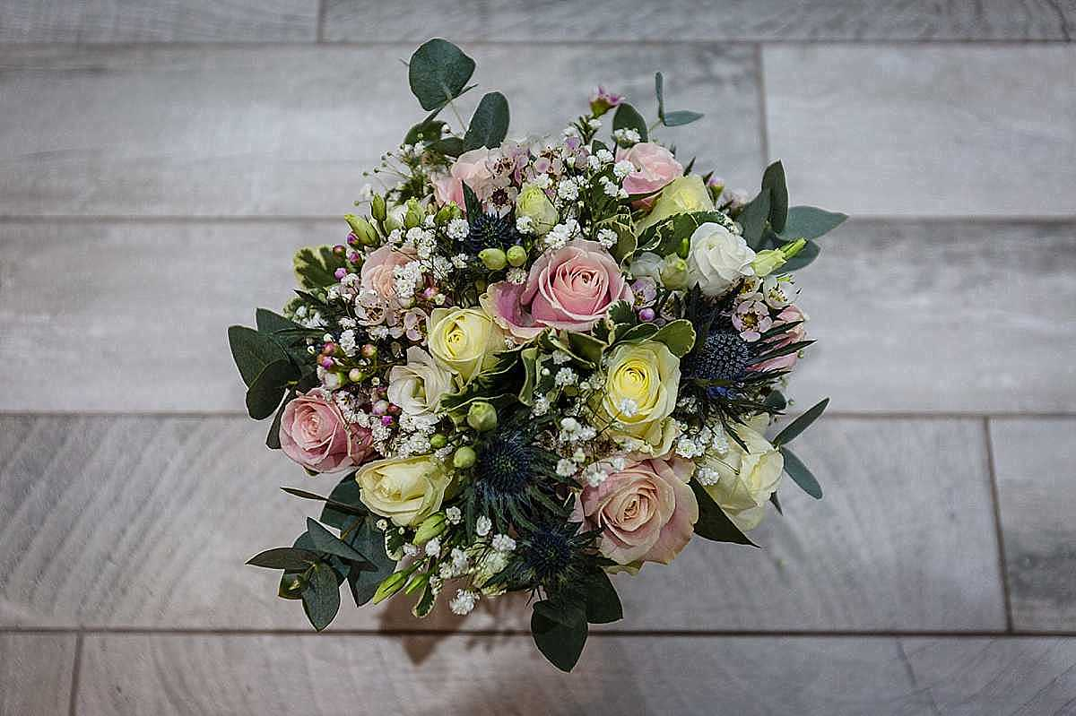 beautiful pastel bouquet of roses, gyp, and thistels for a winter wedding