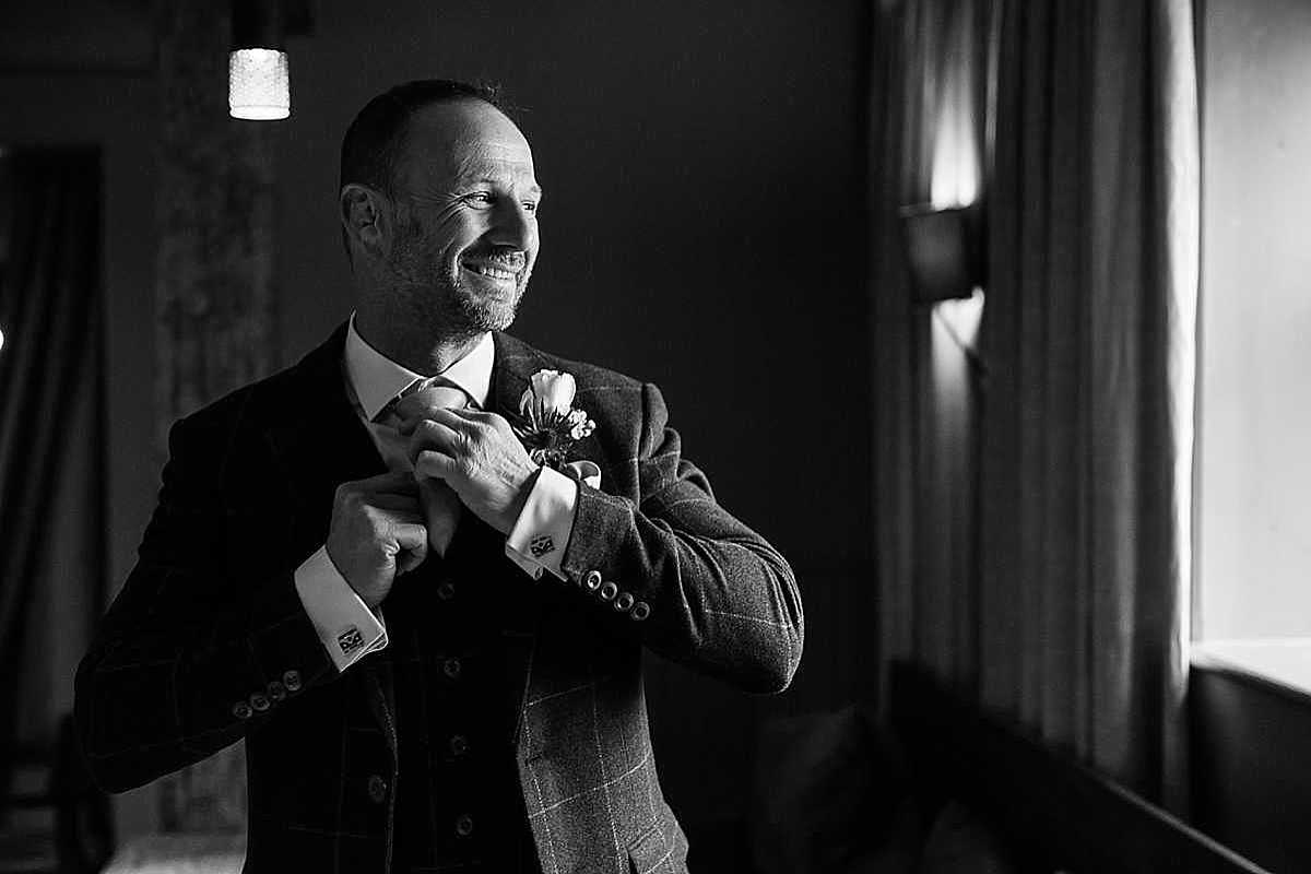 black and white photo of groom altering is tie and looking out of the window looking happy