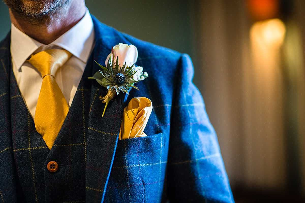 detail shot of golden yellow tie, white rose button hole and yellow pocket square