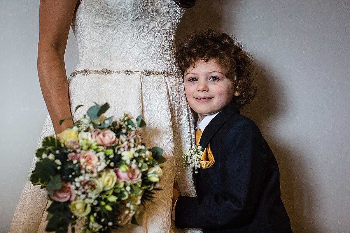 close up of little boy giving his mum a cuddle on her wedding day and close to her wedding dress