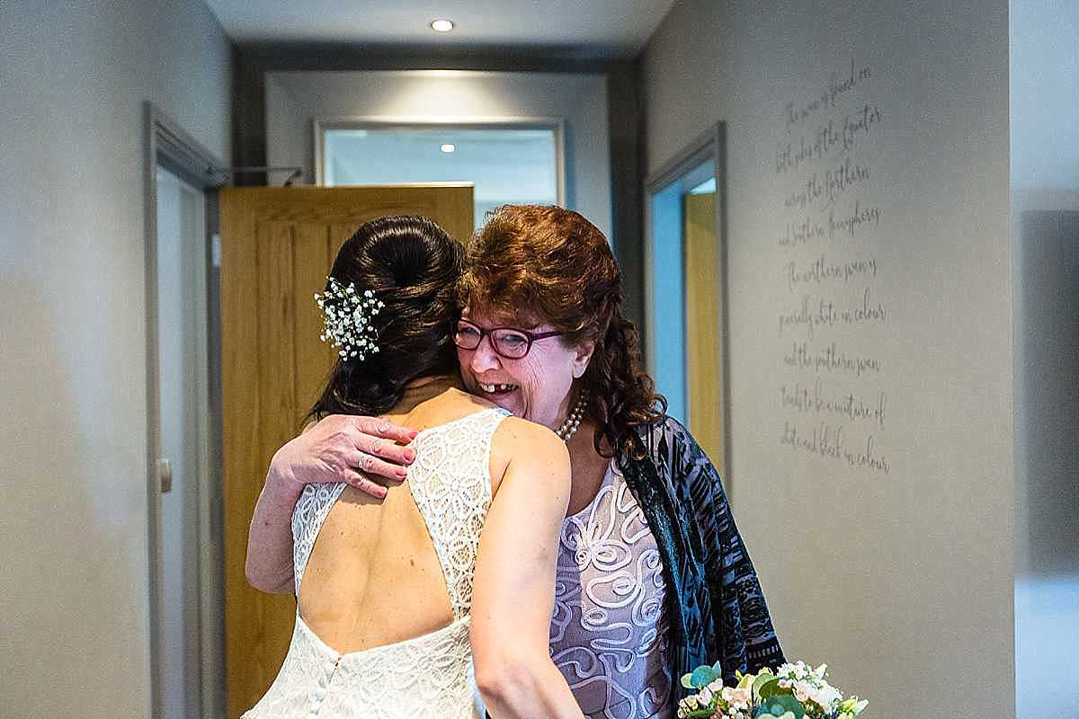 mother of the bride coming in to see her daughter wedding ready and giving her a big cuddle and joyous reaction