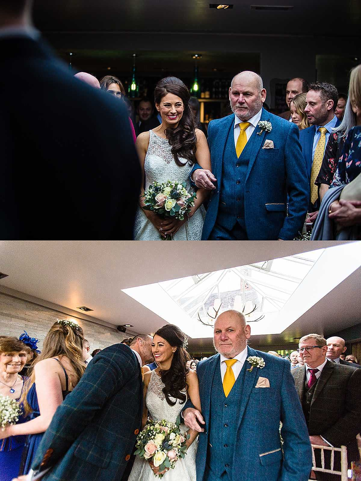 bride walking down the aisle with father of the groom, looking excited as she looks at guest coming down the aisle and groom gives her a kiss