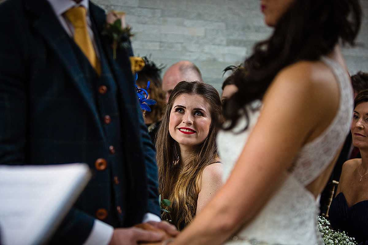 daughter of the groom looking up at dad as he says his vowels and looking incredibly excited and proud holding back the tears]