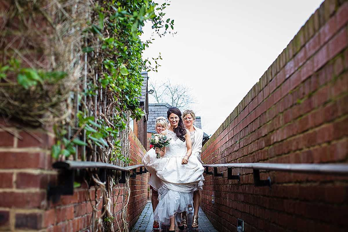 friends carrying the brides dress as she makes her way to the wedding reception