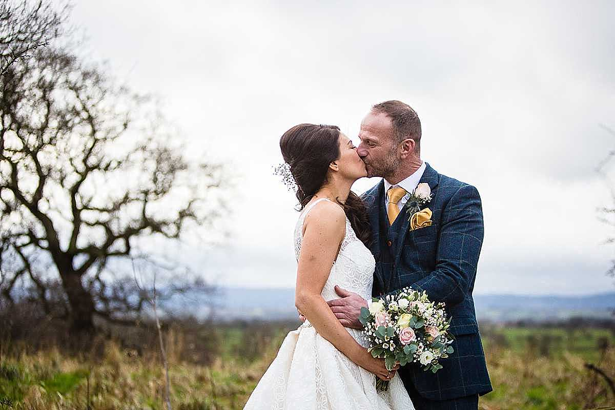 bride and groom having a kiss at cock o barton with cheshire views in the background