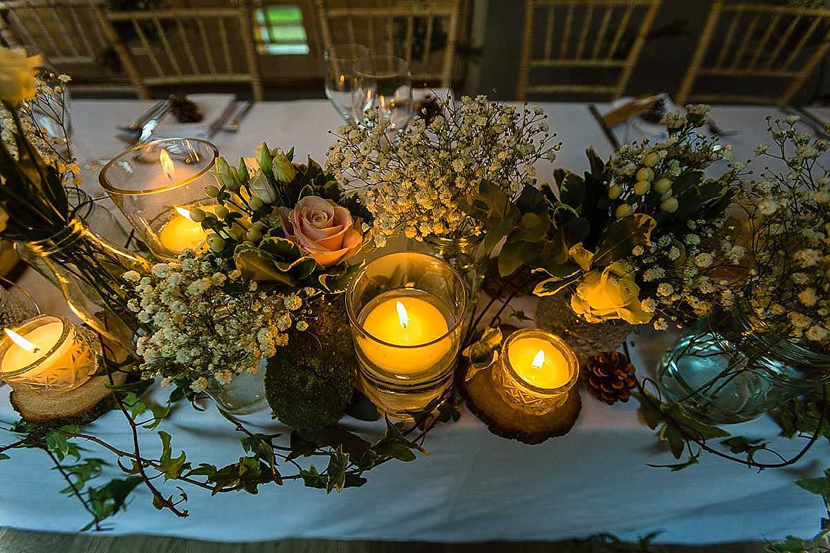 table decor by white wysteria in whitchurch, delicate tiny flowers and wooden logs and little candles