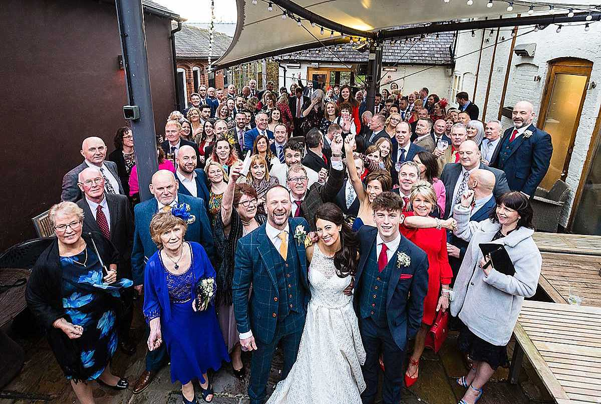 whole group photo of all the guests at cock o barton wedding, taken outside under the canopy
