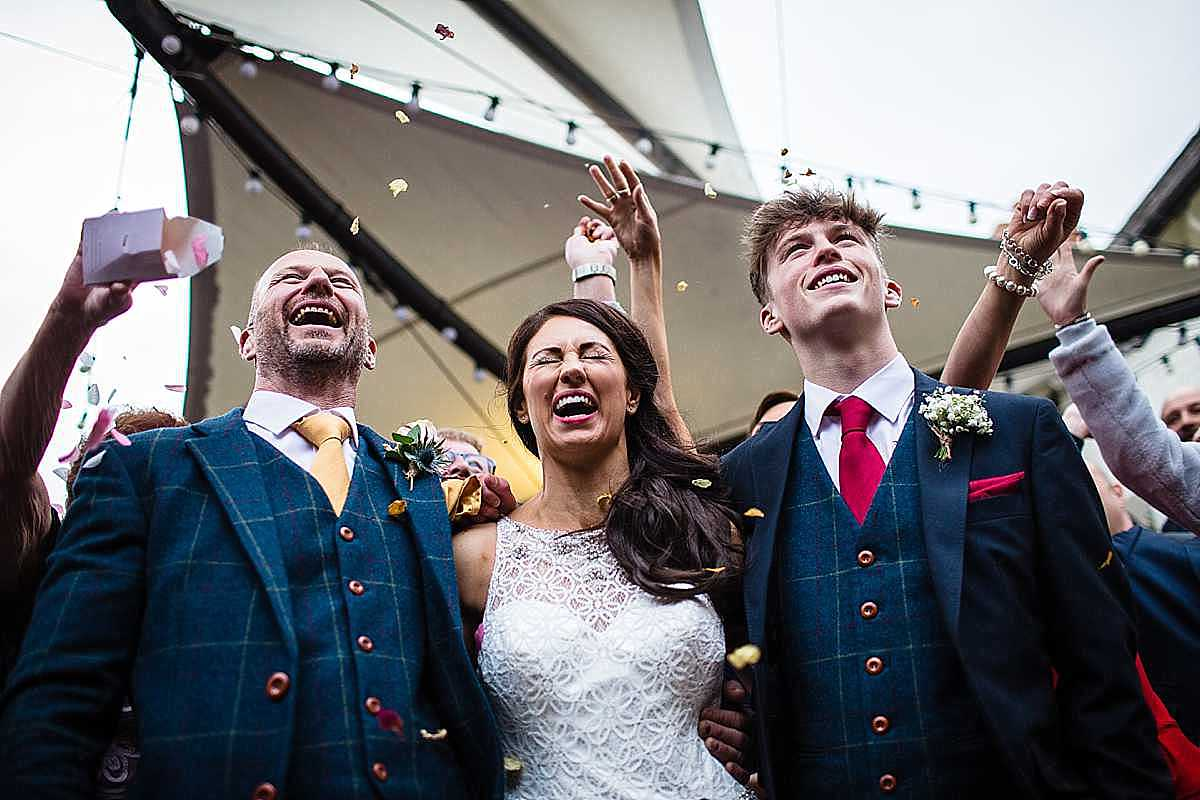 oh my reaction as the bride and groom have confetti thrown over them in the group photo