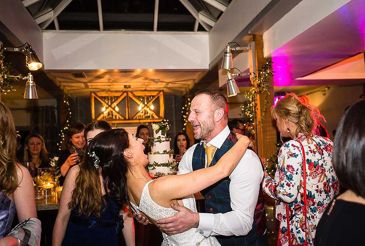 bride and groom singing to each other whilst dancing and leaning back and looking happy
