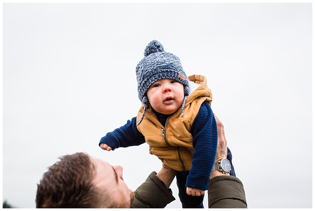 baby boy being lifted up in the air by dad and looking cosy in his wooly hat - shropshire family photographer