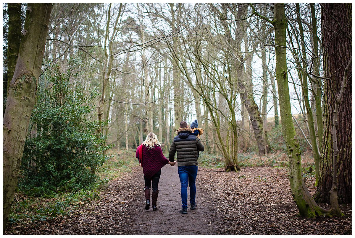 young family walking hand in hand through colemere nature reserve