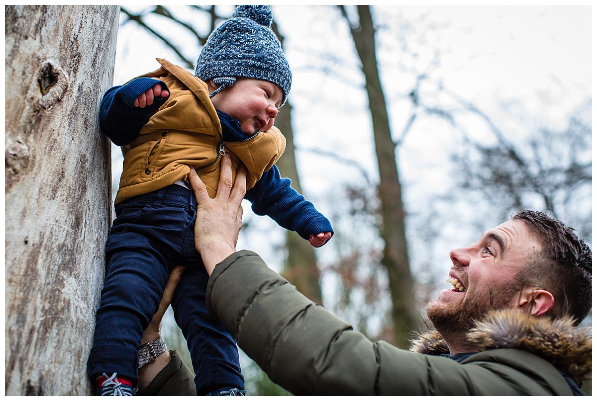 dad holding baby up in the air looking at each other - shropshire family photographer