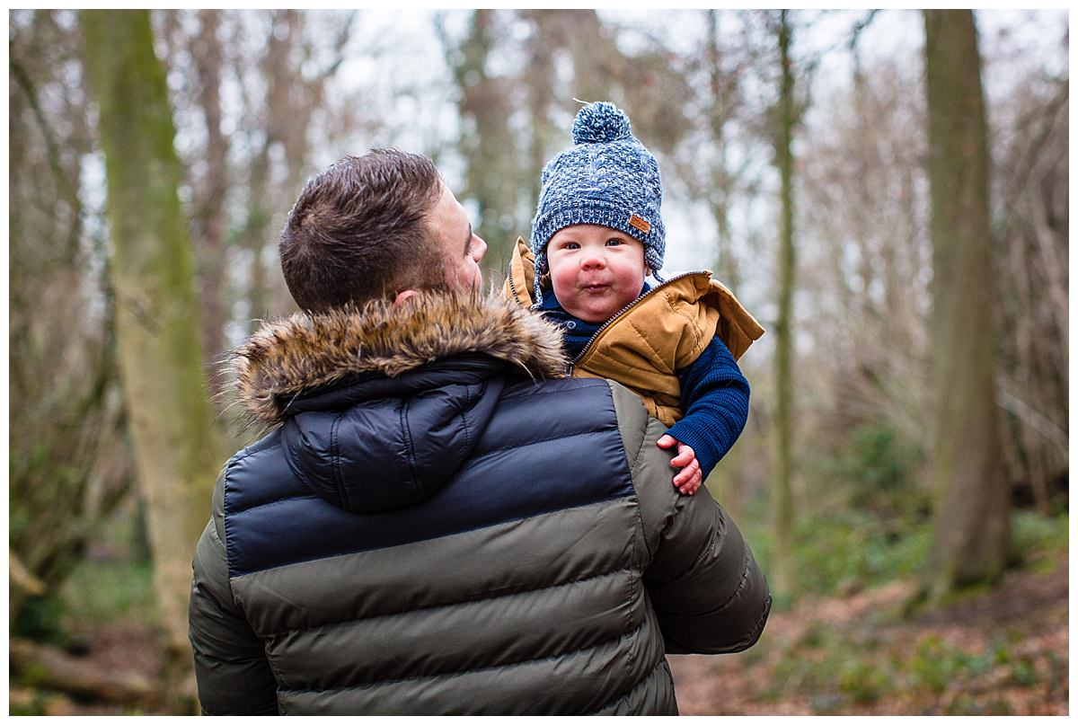 cute blue eyed baby looking over dad's shoulder - family photography shropshire