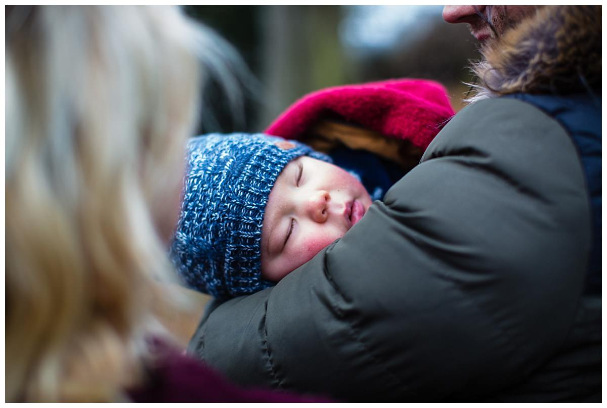 close up shot of baby with lovely rosey cheeks in dad's arms as they walk around colemere nature reserve, shropshire photography