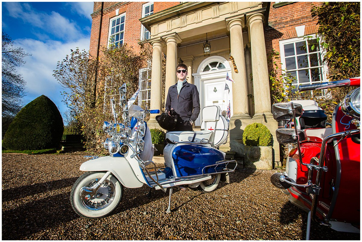 male model wearing liberty fabric tie standing by retro lambretta scooter- styled shoot at Iscoyd Park, Shropshier