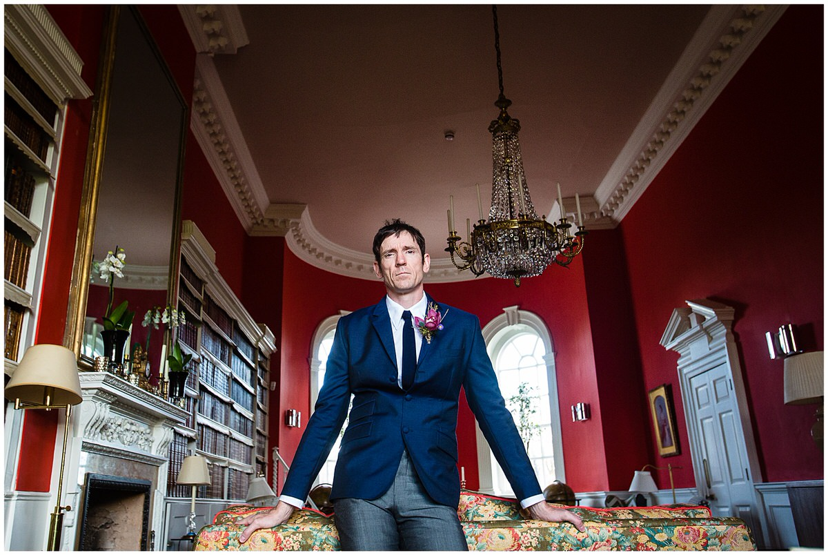 symmetrical shot of groom in knitted tie at iscoyd park holding onto sofa in their recently launched library