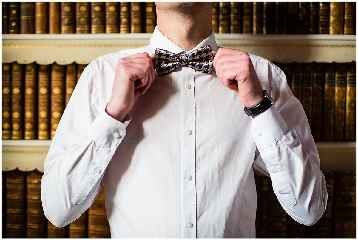close up of groom doing up his bow tie against library books