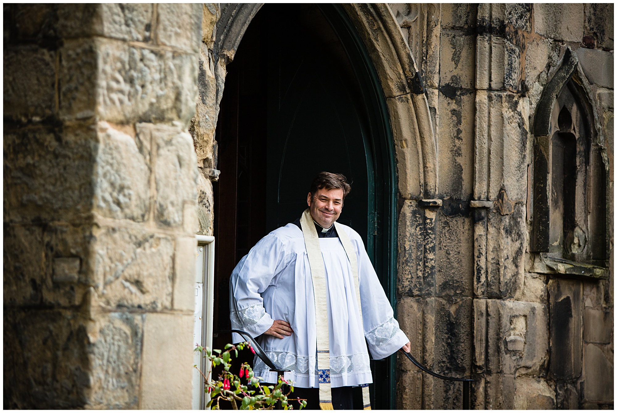 vicar waiting at the door looking very eccited to see the bride
