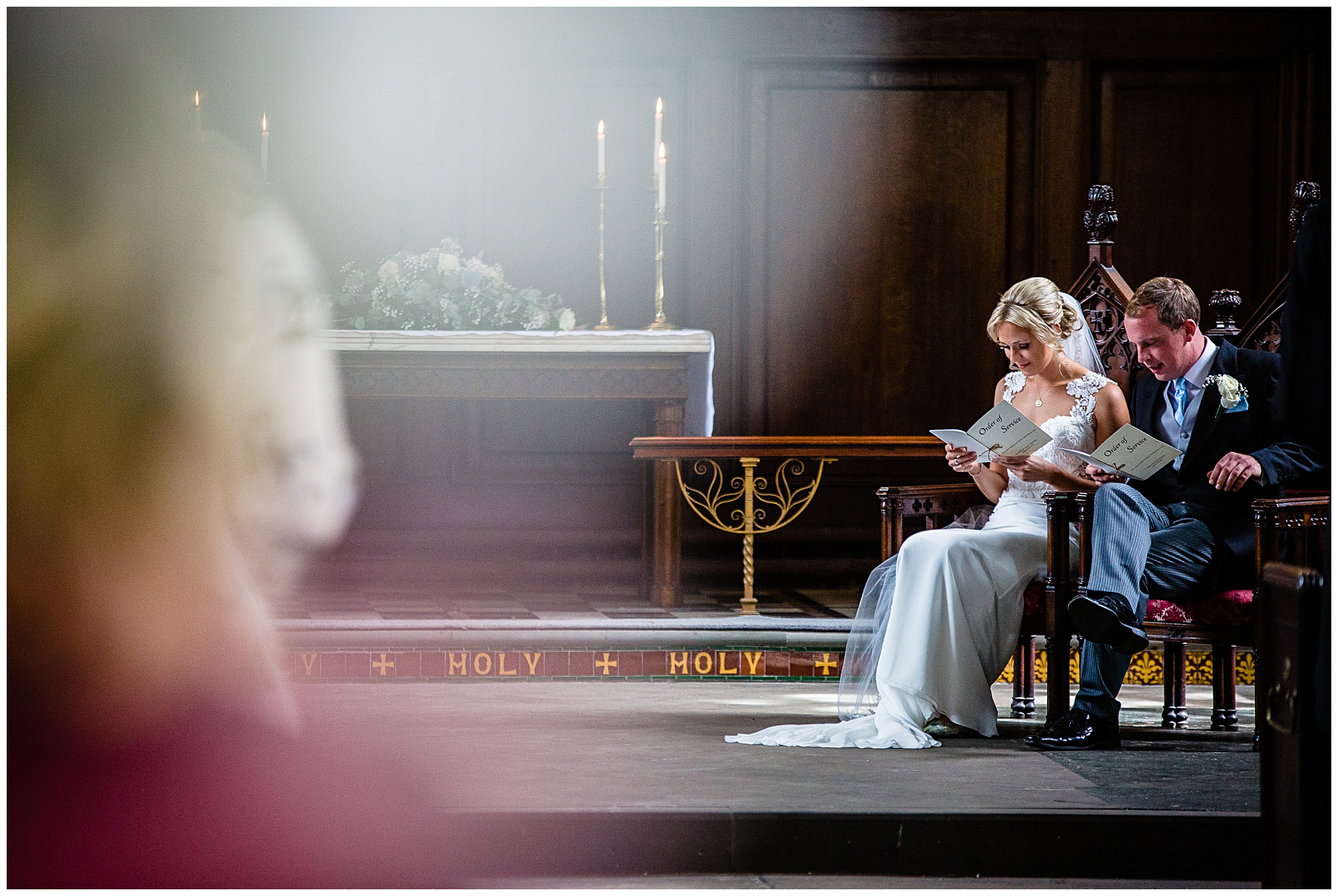 bride and groom sat at the front of church singing a hymn and looing very happy